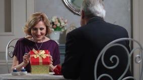 Überraschende reife Dame des alten Mannes mit Geschenk stock video footage