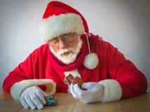 Überraschende Santa Claus-Spiele mit alten Spielwarenautos Stockfoto