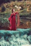 Überraschende Szene mit mittelalterlicher Frau und fliegender Eule nahe Wasserfall lizenzfreies stockfoto