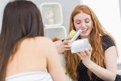 Überraschender blonder Freund der jungen Frau mit einem Geschenk Lizenzfreies Stockfoto