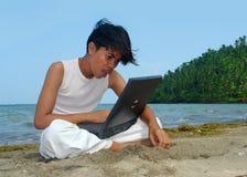 Überraschender Laptop auf dem Strand. Stockfoto