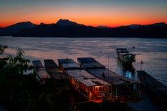 Überraschender Sonnenuntergang in Luang Prabang über dem Mekong Tourist und Hausboote im Wasser Himmel brennt stockfotografie