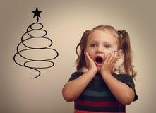 Überraschendes glückliches Mädchen des Spaßes Kinder, dasauf Weihnachtspelzbaum schaut Lizenzfreie Stockbilder