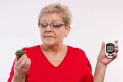 Überraschte ältere Frau, die glucometer und frischen kleinen Kuchen hält, Zuckergehalt, Konzept von Diabetes misst und überprüft Lizenzfreie Stockbilder