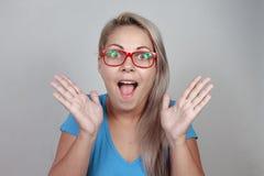 Überraschte blonde Frau in den roten Gläsern Lizenzfreie Stockfotos