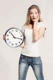 Überraschte attraktive junge Frau, die große Uhr hält Lizenzfreie Stockfotografie