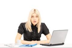Überraschte blonde Frau, die auf einer Tabelle in ihrem Büro sitzt Lizenzfreies Stockbild