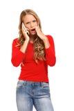 Überraschte blonde Frau, die auf Mobiltelefon spricht Lizenzfreie Stockfotografie