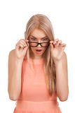 Überraschte blonde Frau, die unten über Gläsern schaut Lizenzfreies Stockbild