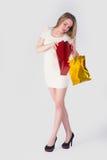 Überraschte blonde Frau mit Einkaufstaschen Lizenzfreies Stockfoto