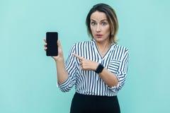 Überraschte blonde Geschäftsfrau, die Finger auf intelligentes Telefon zeigt und Stockfotos