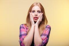 Überraschte blonde junge Frau, die Kamera betrachtet Lizenzfreie Stockfotos