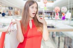 Überraschte Einkaufsfrau mit Taschen in der großen Mallmitte Stockfotografie
