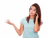 Überraschte erwachsene Frau, die auf ihrem Mobiltelefon sich unterhält Stockbild