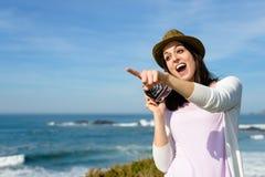 Überraschte flippige Frau, die Foto zum Meer macht Stockfotografie