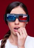 Überraschte Frau in den Stereogläsern Stockfoto