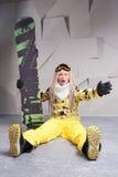 Überraschte Frau, die auf Boden mit Snowboard sitzt Stockbild