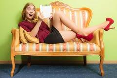 Überraschte Frau, die auf Sofa mit PC-Tablette legt Stockfotografie
