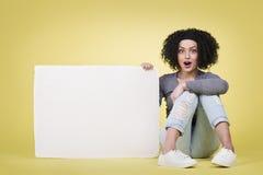 Überraschte Frau, die ein weißes Zeichenbrett hält Lizenzfreie Stockbilder