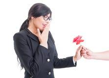 Überraschte Frau, die eine Blume empfängt Lizenzfreie Stockfotografie