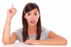 Überraschte Frau, die herauf ihren Finger zeigt Lizenzfreie Stockfotos