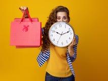 Überraschte Frau, die hinter Uhr sich versteckt und Einkaufstaschen zeigt Lizenzfreie Stockfotos