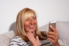 Überraschte Frau, die ihr Telefon betrachtet Lizenzfreies Stockbild