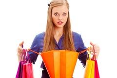 Überraschte Frau, die mit geöffneter Einkaufstasche steht Lizenzfreie Stockfotos