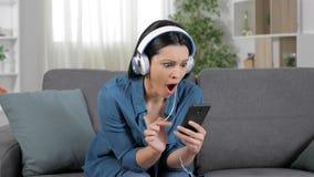 Überraschte Frau, die Musik vom Handy hört