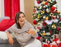 Überraschte Frau, die Nahe Weihnachtsbaum fernsieht Lizenzfreie Stockfotografie