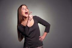 Überraschte Frau, die oben lacht und zeigt Stockfotos