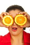 Überraschte Frau, die orange Scheiben anhält Stockfotografie