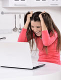 Überraschte Frau, die rückwärts mit Laptop schaut Stockbilder