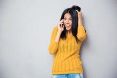 Überraschte Frau, die am Telefon spricht Stockbilder