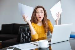 Überraschte Frau, die am Tisch mit Rechnungen sitzt Stockfotografie