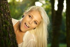 Überraschte Frau hinter Baum Lizenzfreies Stockfoto