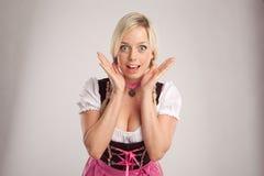 Überraschte Frau mit Dirndl Stockfotografie