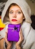 Überraschte Frau mit einem Geschenk stockbilder