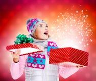 Überraschte Frau mit einem Weihnachtsgeschenk mit dem magischen Glänzen von b Stockfotografie