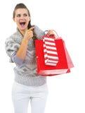Überraschte Frau mit Einkaufstaschen zeigend auf Kopienraum Lizenzfreies Stockfoto