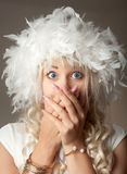 Überraschte Frau mit großen blauen Augen und einem Federhut Stockbilder