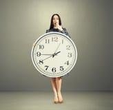 Überraschte Frau mit großer weißer Uhr Lizenzfreies Stockfoto