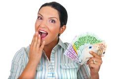Überraschte Frau mit Handvoll Geld stockfotografie