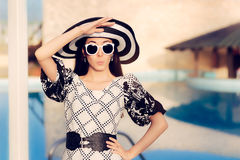 Überraschte Frau mit Sonnenbrille und Sun-Hut durch das Pool Stockfotografie