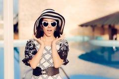 Überraschte Frau mit Sonnenbrille und Sun-Hut durch das Pool Stockfoto