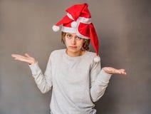 Überraschte Frau in Sankt-Hüten ihre Schultern zuckend lizenzfreies stockbild