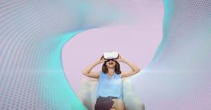 Überraschte Frau in VR-Kopfhörer, der Lichter gegen rosa Hintergrund betrachtet Stockfoto