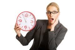 Überraschte Geschäftsfrau, die eine große Uhr hält Stockbilder