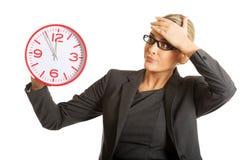 Überraschte Geschäftsfrau, die eine große Uhr hält Stockbild