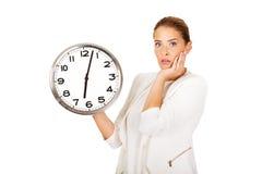Überraschte Geschäftsfrau, die eine große Uhr hält Lizenzfreie Stockfotografie
